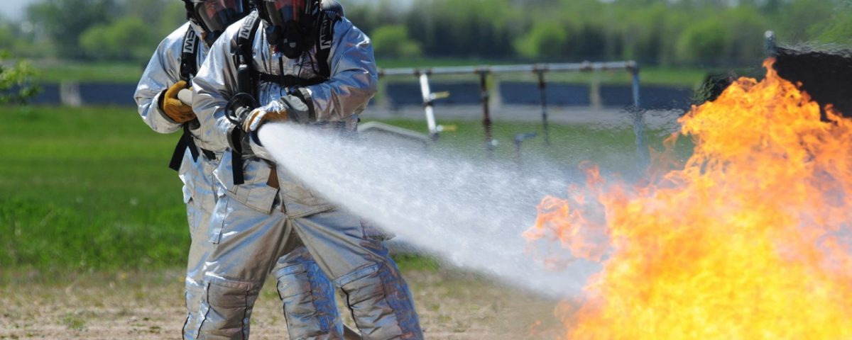 Master Sgt. Joel Anderson, of the 148th Fighter Wing, right, and Tech. Sgt. Alex Stuart, of the 133rd Airlift Squadron, form a two-person fire fighter hose team, May 19, at the North Dakota Air National Guard Regional Training Site.  The fire fighters are spraying water on a mock aircraft burn pit fire to fulfill annual fire fighter training requirements.